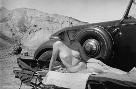 Lee Miller sunbathing nude beside her car, Egypt